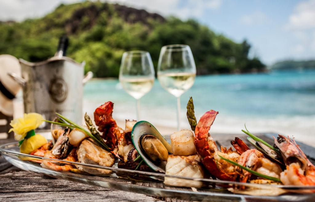 Beau plateau de fruits de mer et vin blanc sur une plage paradisiaque