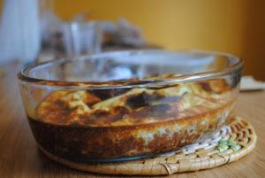 Plat en verre rempli de bobotie gratiné au four sur un sous plat