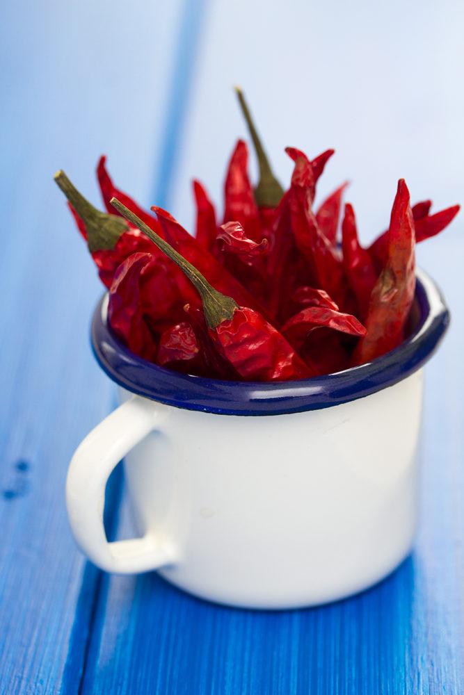Tasse métallique remplie de piment peri peri rouges séchés