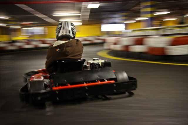 Un petit garcon roule a plein regime sur la piste de karting muni de son casque