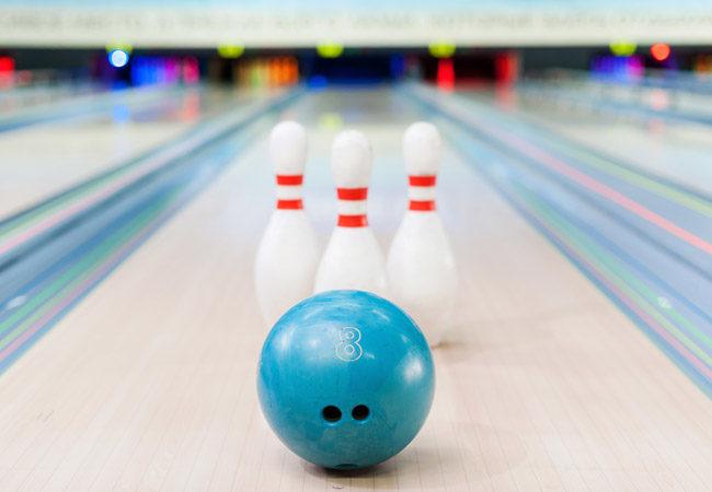 Une boule bleue et trois quilles de bowling sont disposes sur la piste