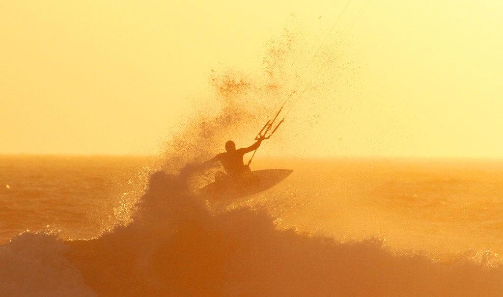 Vue sur un kitesurfer en pleine action au coucher du soleil orangé