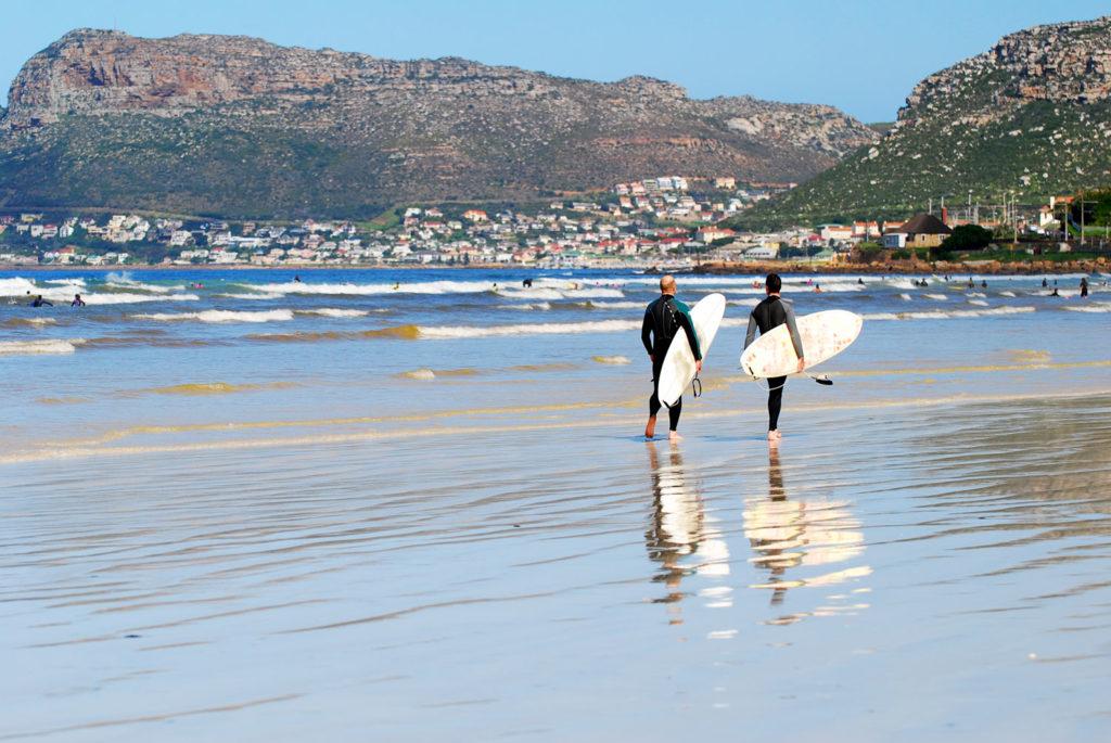 Deux surfers marchent sur la plage de Muizenberg face aux montagnes