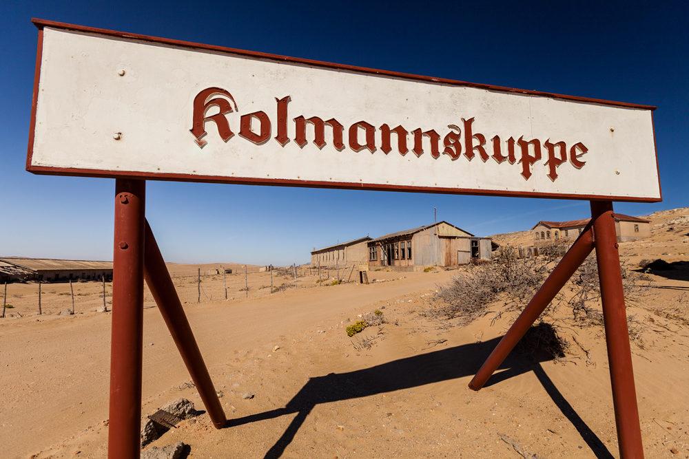 Gros plan sur le panneau de Kolmanskop avec derrière la ville ensablée