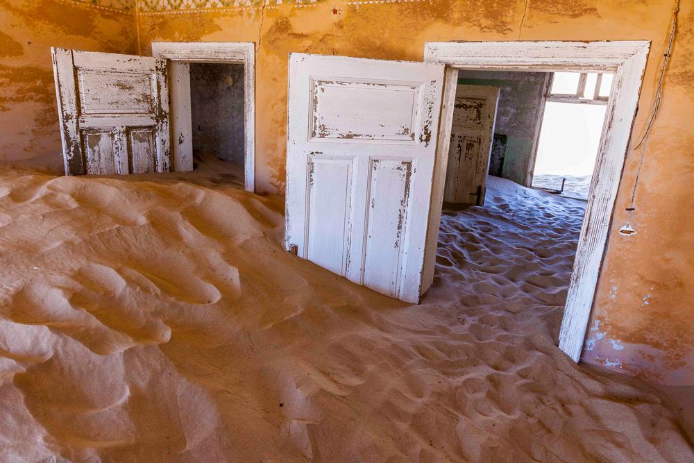 Deux portes ouvertes ensablées dans une pièce orangée abandonnée