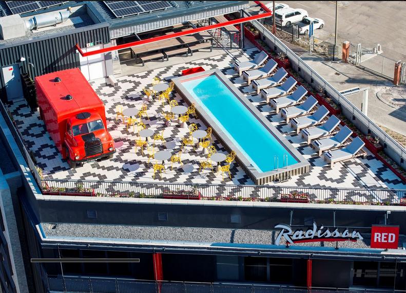 Vue du ciel, zoom sur le rooftop avec sa piscine et son camion rouge