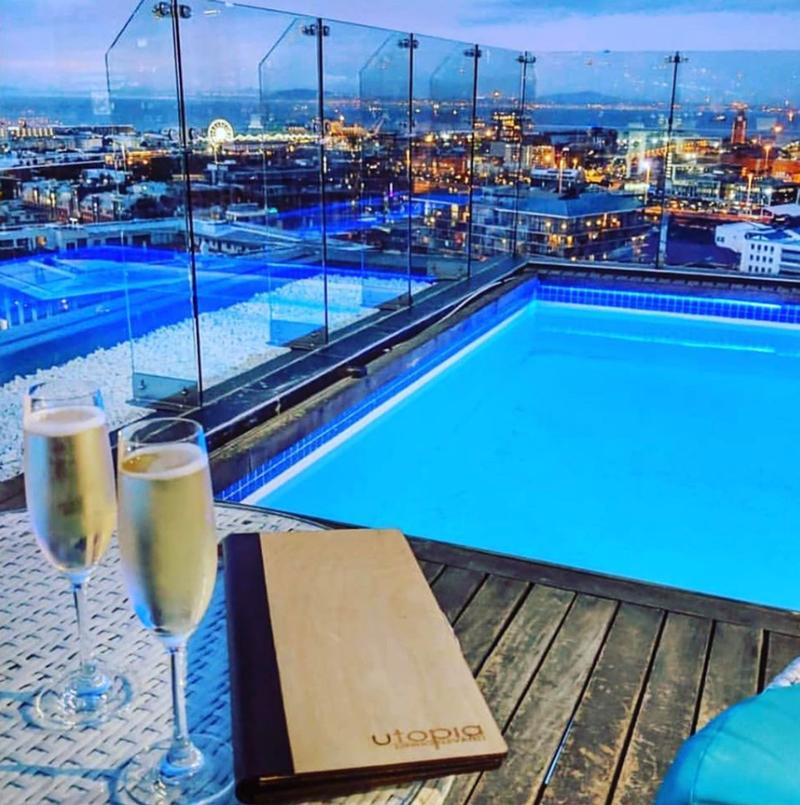 2 cocktails à côté de la piscine avec vue sur la ville et ses lumières