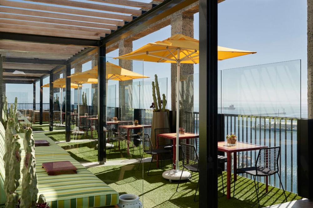 Les banquettes, tables, parasols et gazon synthétique du rooftop silo