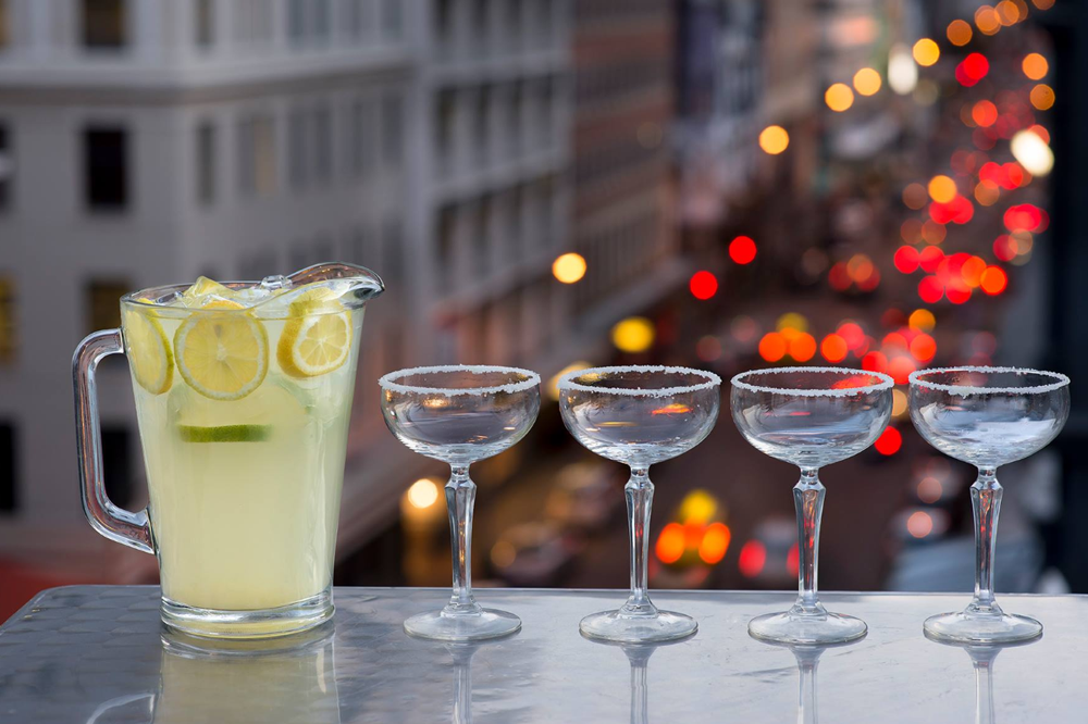 4 verres à cocktail de margarita avec en fond les lumières de la rue