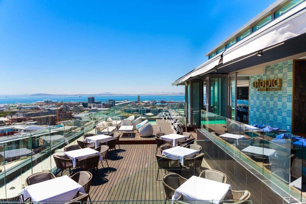 Le toit-terrasse en bois d'Utopia donnant sur la ville et l'océan