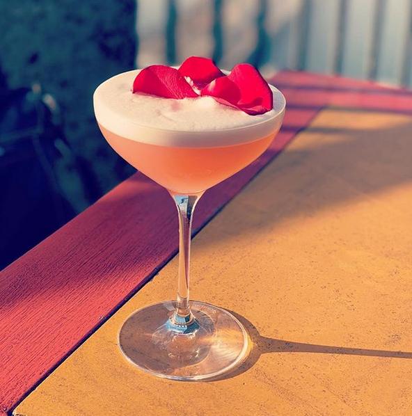 Zoom sur un cocktail et ses pétales de fleur délicatement posées dessus