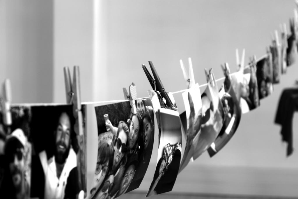 Photo en noir et blanc avec pleins de Polaroïds de l'équipe suspendus