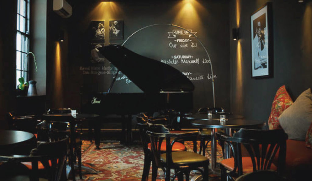 L'intérieur du piano bar avec son piano à queue et son ambiance cosy