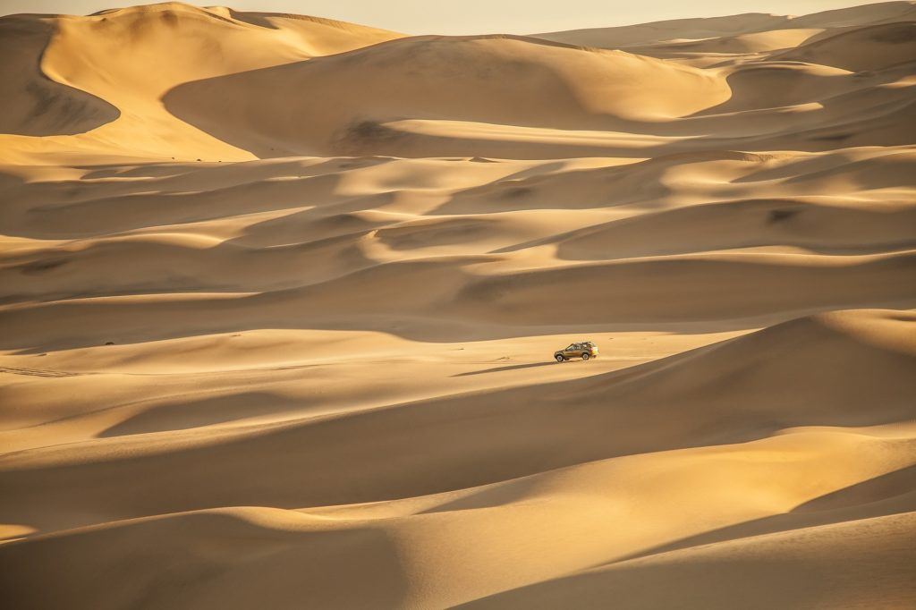 Vue sur les dunes infinies du désert du Namib où un 4x4 roule