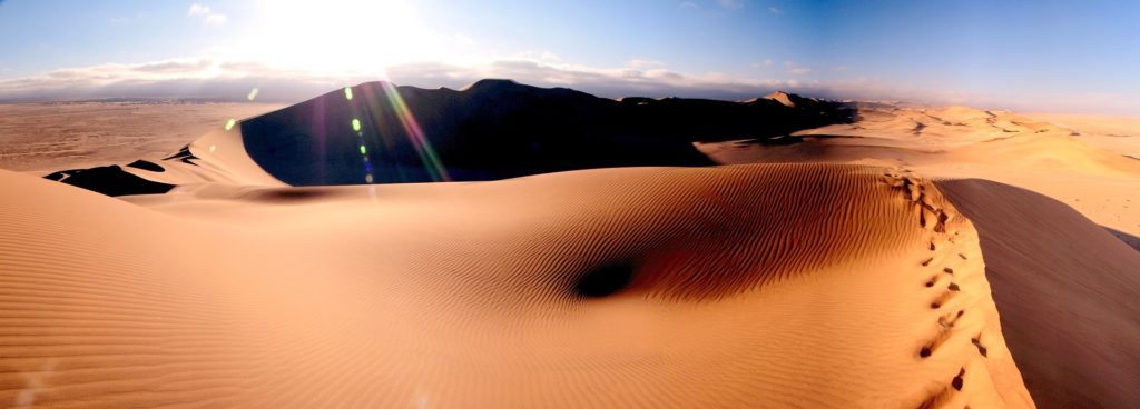 Sous un grand ciel bleu, le soleil brille au firmament sur les dunes