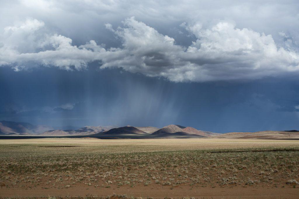 Ciel sombre chargé de nuages et de pluie sur un paysage aride
