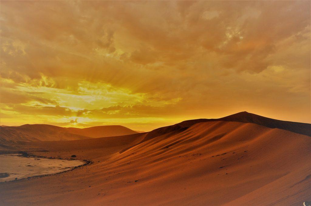 Chaleur dans les dunes avec un ciel nuageux orangé par le soleil