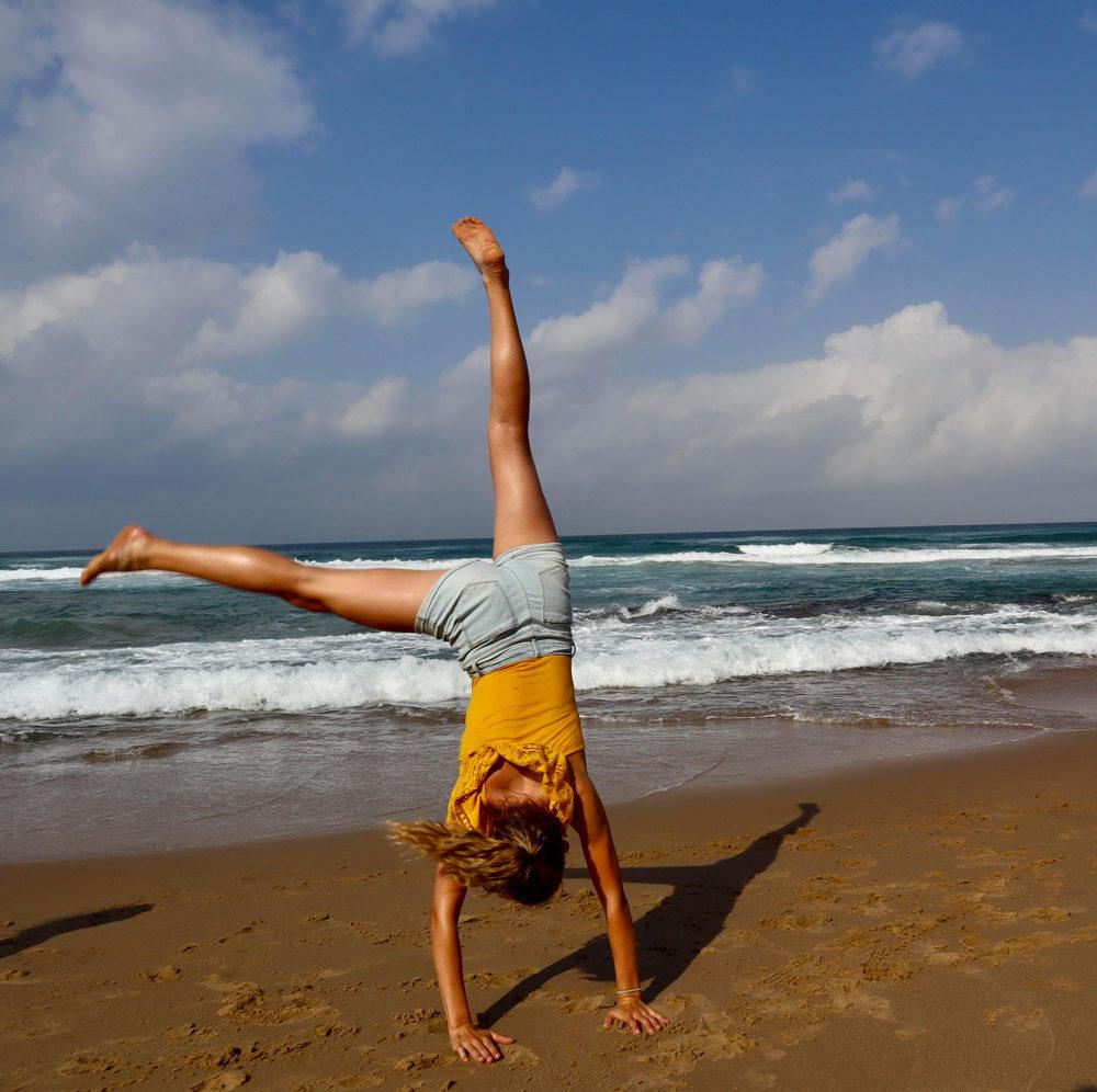 Une adolescente fait la roue sur une plage sauvage de la Garden Route
