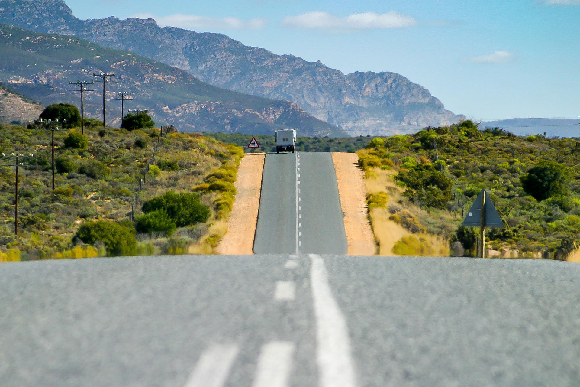 Route scénique jusqu'à l'horizon avec un camping-car au loin