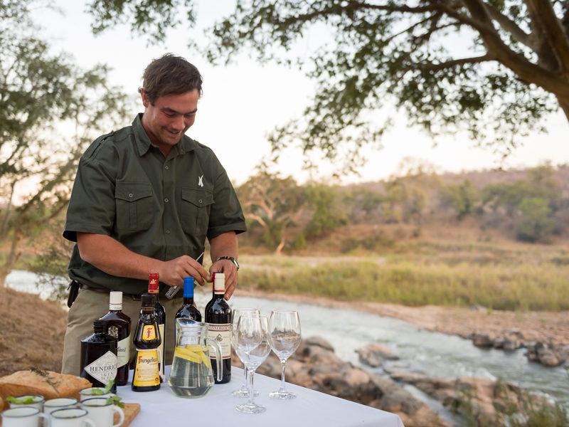 Un ranger va servir des verres lors d'une pause privative en brousse