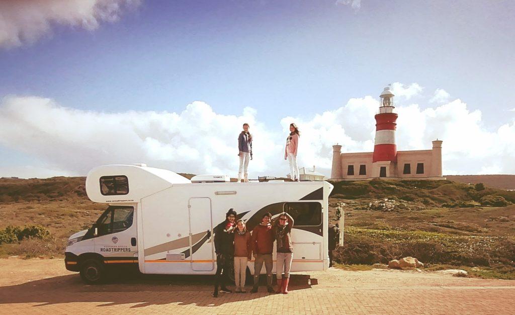 Une famille pose devant un camping car avec les enfants sur le toit