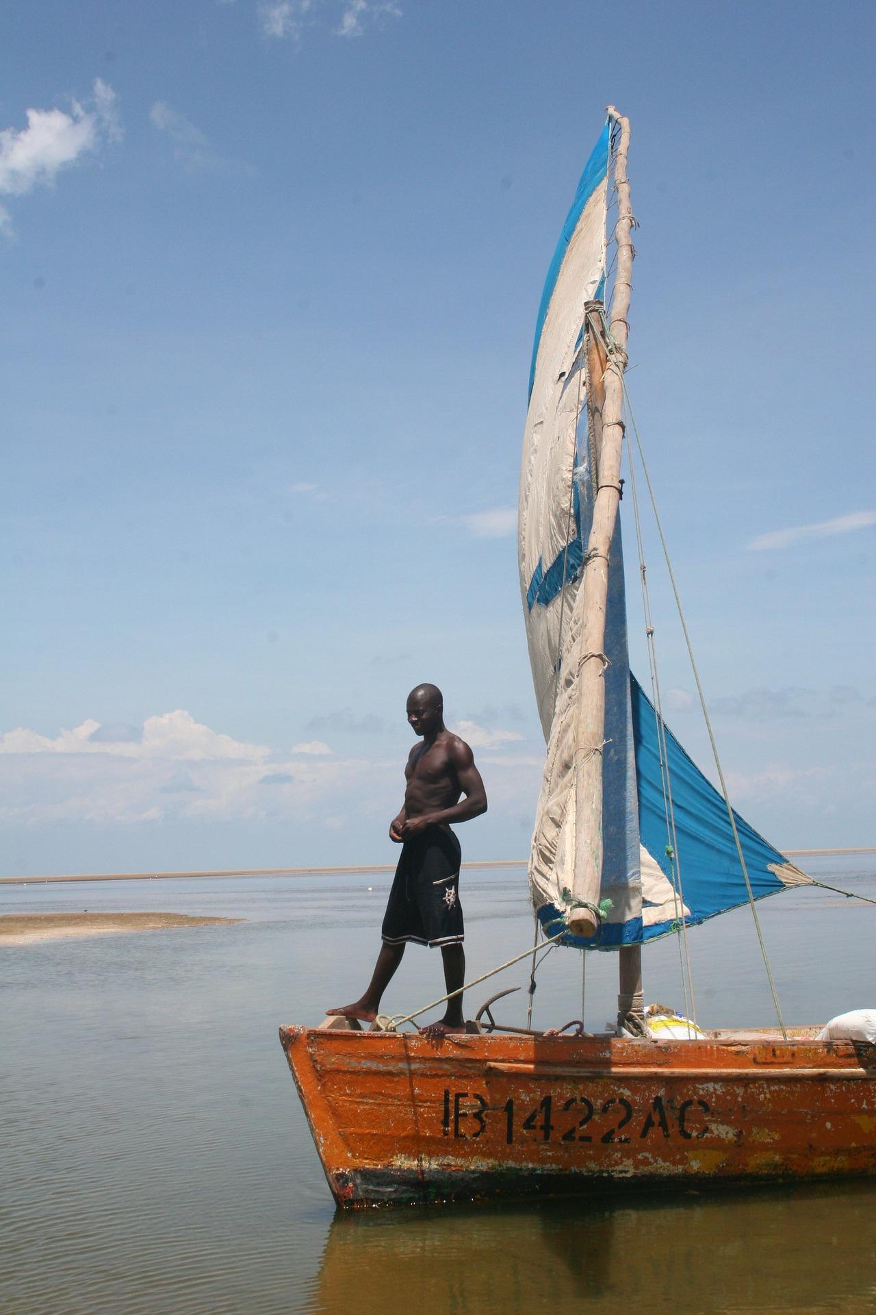 Un homme debout sur un boutre, dans les eaux du Mozambique